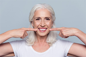 Older woman pointing to smile