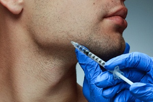 person receiving a BOTOX injection into their chin