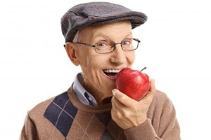 An older man biting into an apple