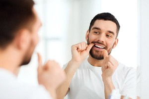 A man flossing his teeth in the mirror