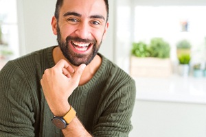 A young man wearing a green sweater and watch showing off his new smile thanks to dental implants
