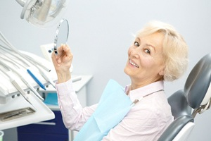 An older woman holding a handheld mirror while seated in the dentist's chair and smiling after receiving new dentures