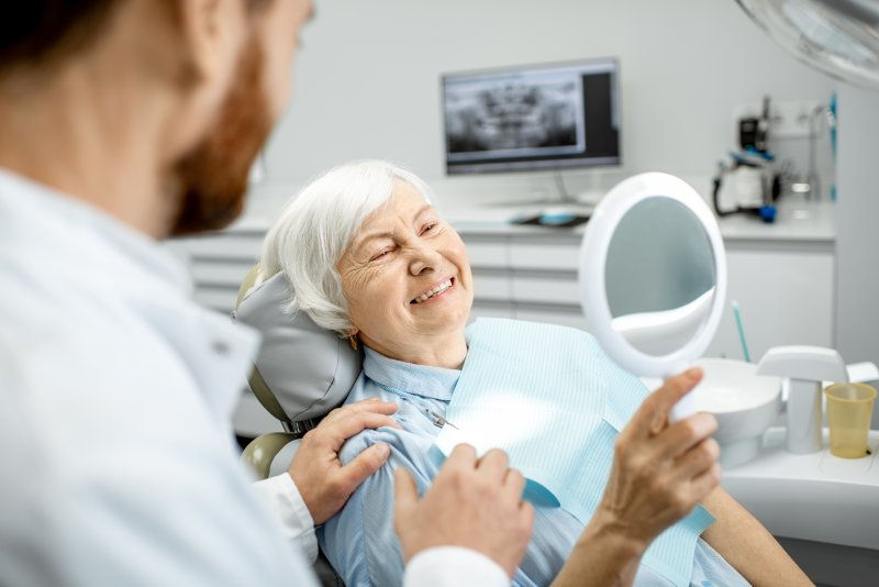 older woman in dentist chair smiling after dental implants