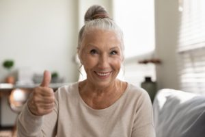 Woman with All-on-4 implant dentures gives thumbs-up
